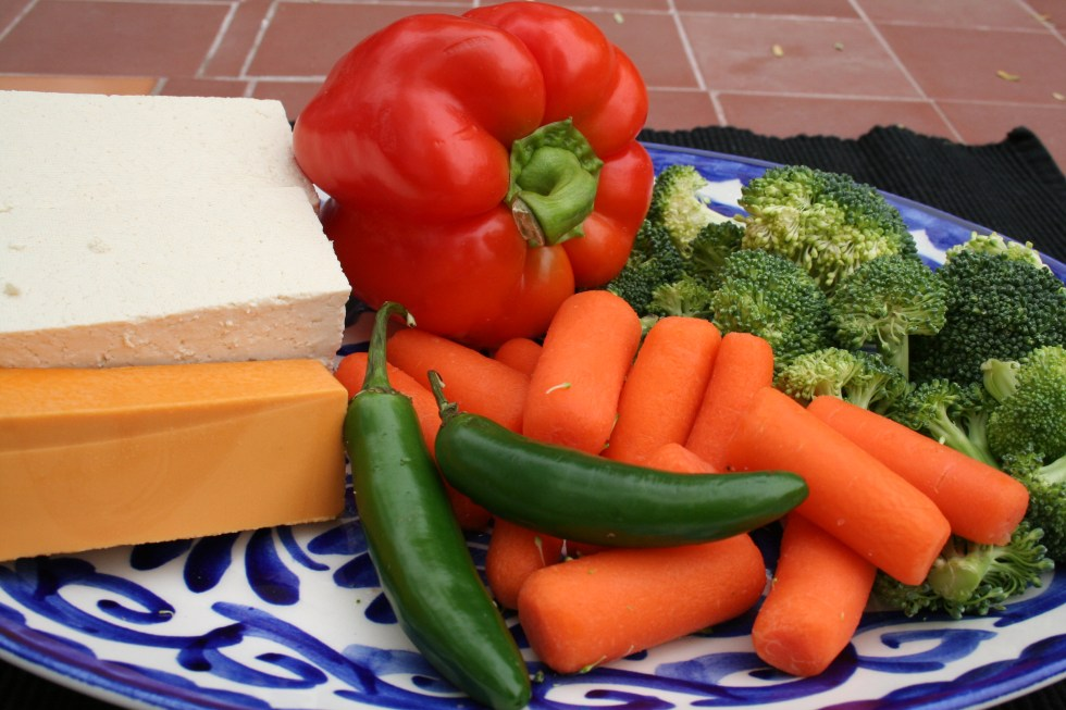 Plate with tofu, vegan cheese, red pepper, broccoli, carrots, and serrano pepper.