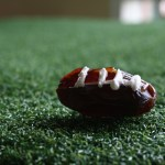 Stuffed Date Football close up on a fake grassy field.