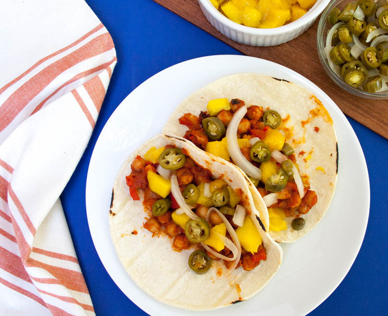 BBQ Chickpea and Mango Tacos with Pickled Peppers and Onions vertical with chopped mango and pickled peppers and onions in the corner.