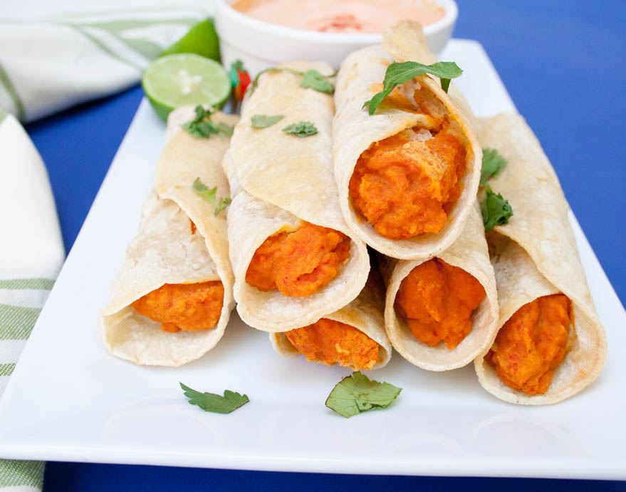 Chickpea and Roasted Red Pepper Taquitos with Harissa Cream close up.