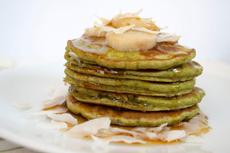 Matcha Banana Pancakes stacked with sliced banana and coconut flakes.