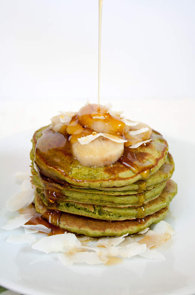 Matcha Banana Pancakes with maple syrup being poured on them