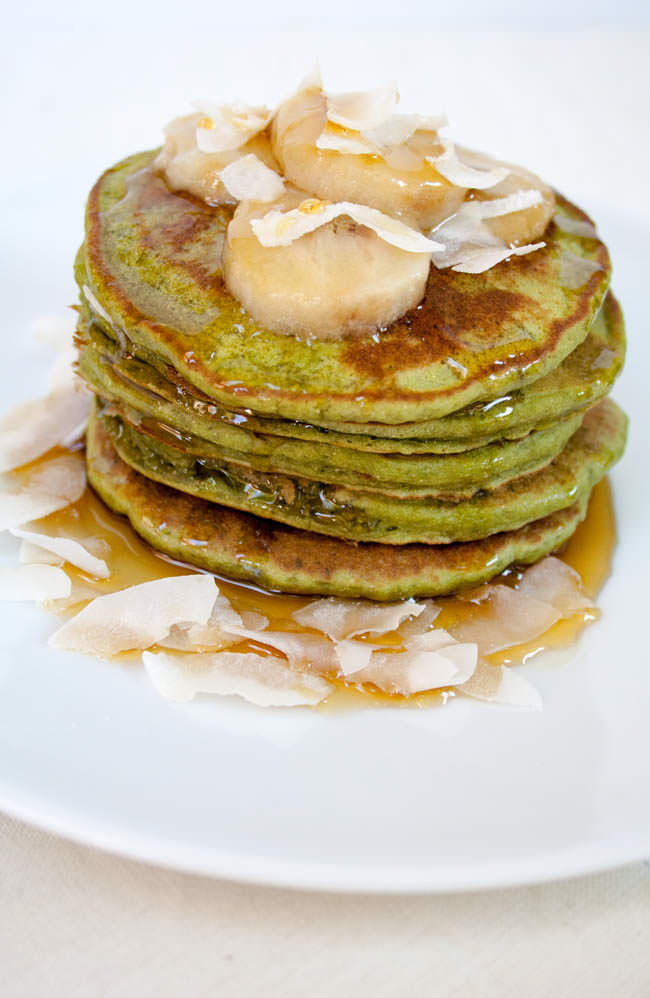 Matcha Banana Pancakes on a plate with maple syrup, sliced banana, and coconut flakes.