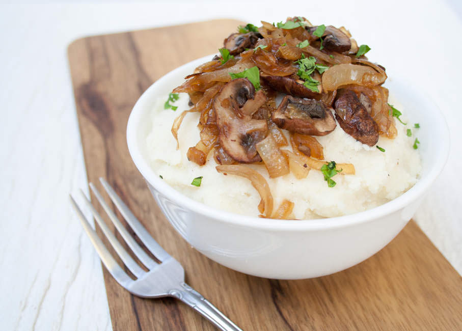 Vegan Mashed Cauliflower with Caramelized Onions and Mushrooms in a bowl with fork.