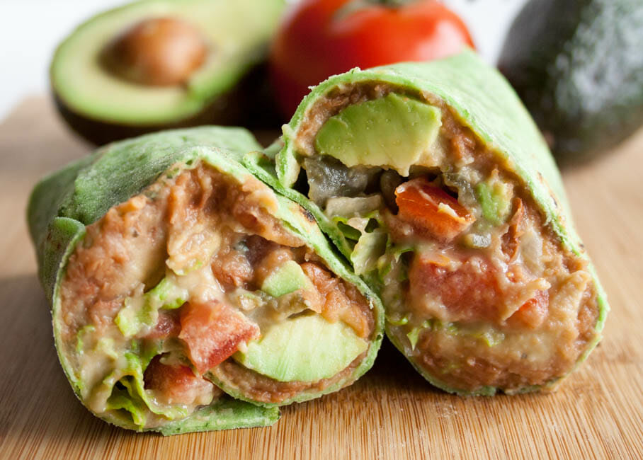 Vegan Refried Bean Burrito with Jalapeño Cilantro Hummus close up with avocados and tomatoes in the background.