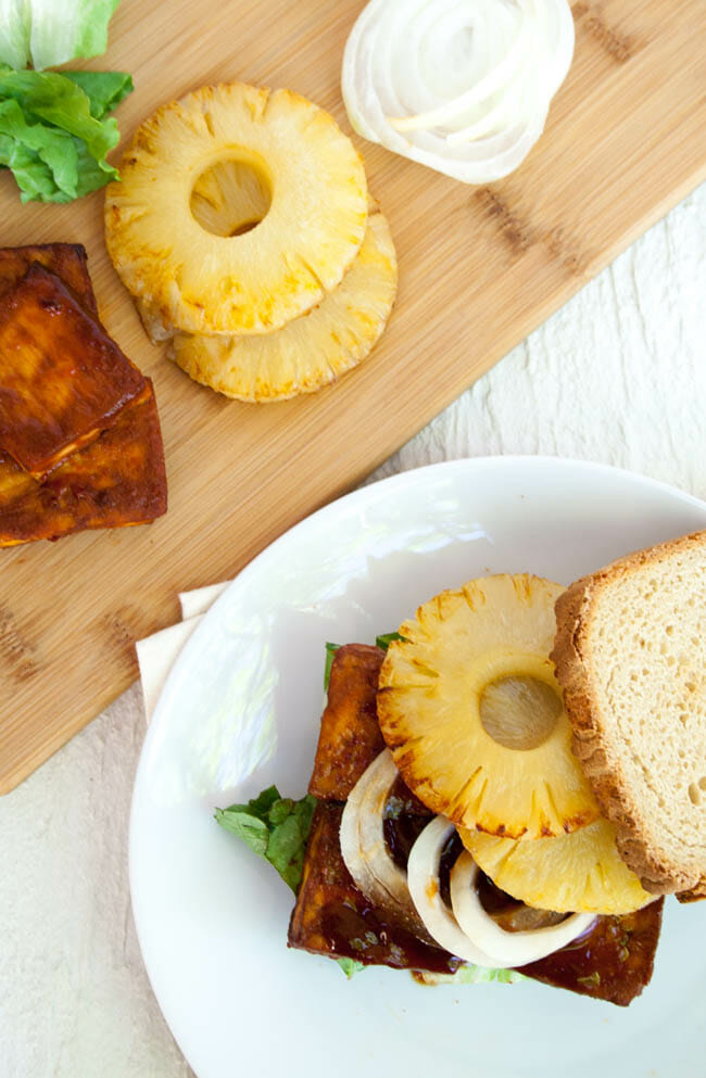 Baked BBQ Tofu Sandwich next to cutting board with baked BBQ tofu, pineapple, lettuce, and onion.