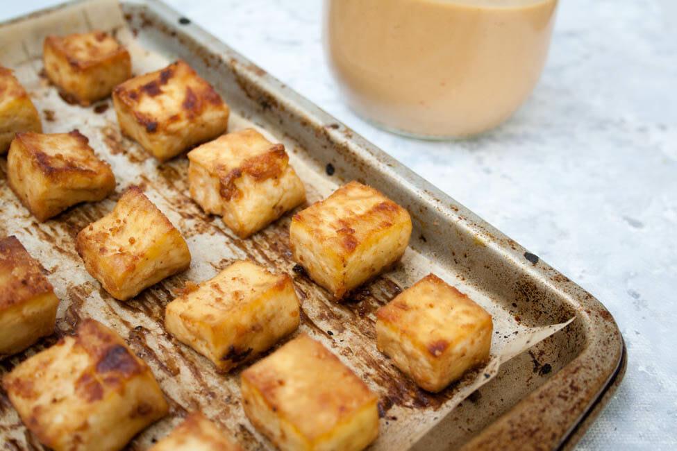 Crispy Baked Tofu with Peanut Sauce on baking sheet
