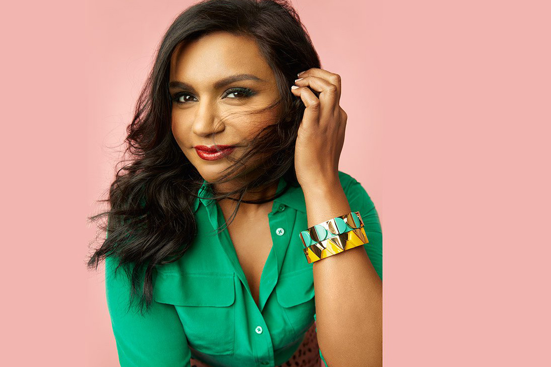 Mindy Kaling Looking Straight at Camera, brushing Hair behind her left ear