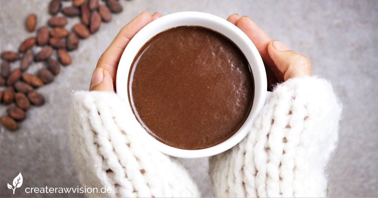 Gesunder Kaffee-Ersatz - Dr. Switzers Karob-Kaffee Tonikum in einer Tasse, die von Händen gehalten wird. Daneben Kakaobohnen