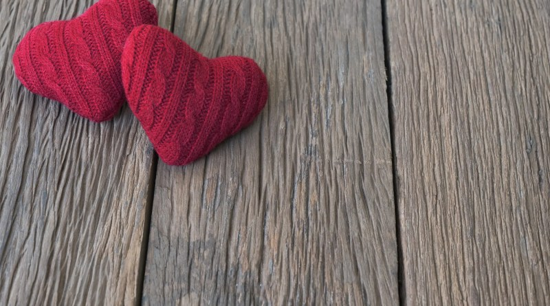 Two handmade knit red hearts on rustic wooden table