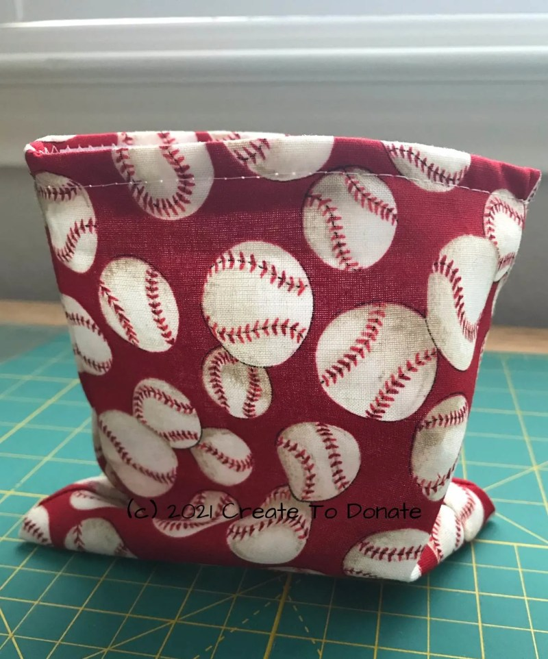 Resuable snack bag in cotton fabric with baseballs on a red background..