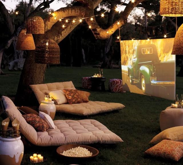Aménagement d'un cinéma en plein air avec coussin, pop corn, guirlande lumineuse et grand écran dans le jardin : c'est l'été