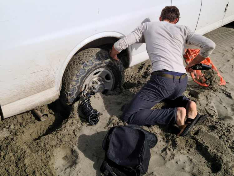 Man digging van out of sand