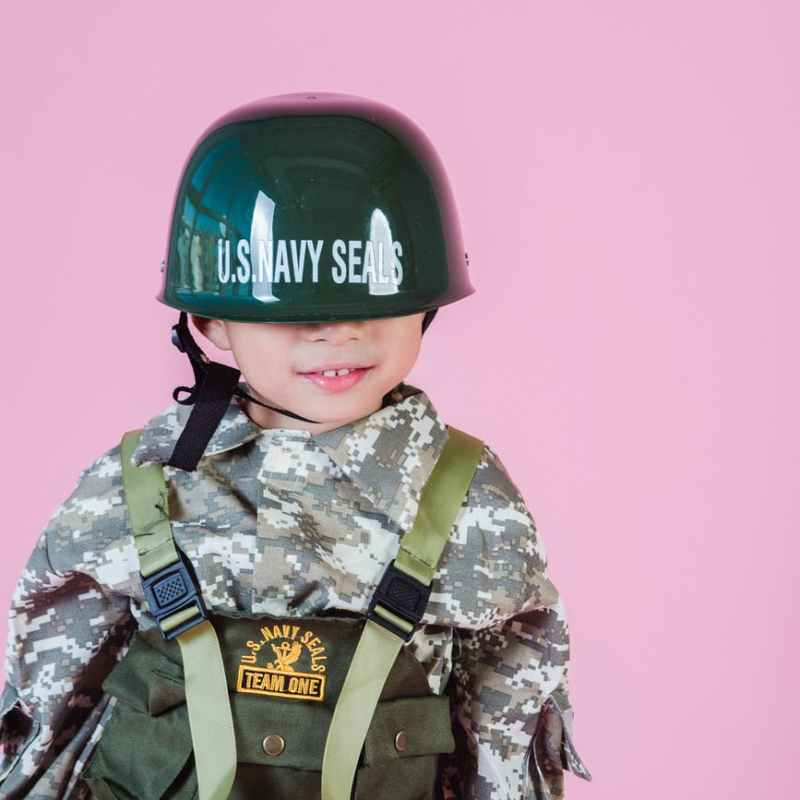 cute boy in military uniform against pink background