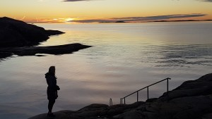 Kvinna i framför en solnedgång.