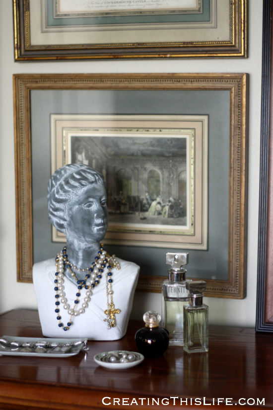 vintage framed prints and bust with rosarys and pearls in master bedroom