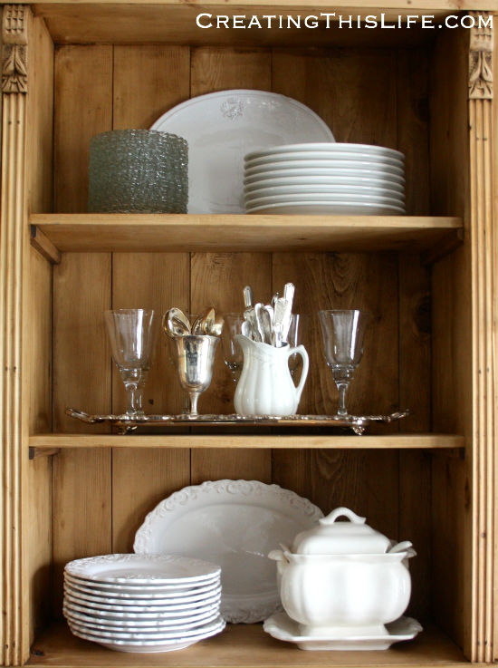 pine hutch with white dishes and silver
