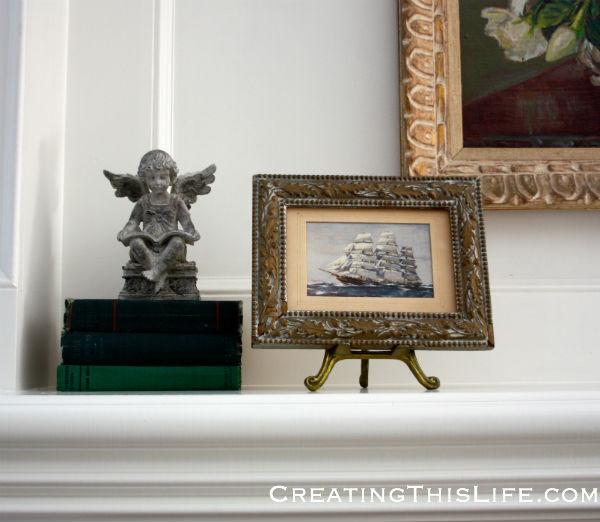 Framed postcard garden statue books on mantle