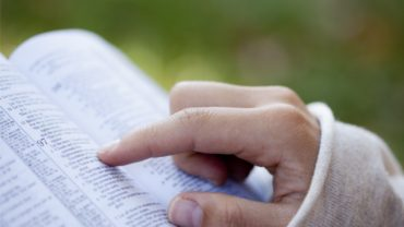 close-up-of-womans-hands-while-reading-the-bible-outside