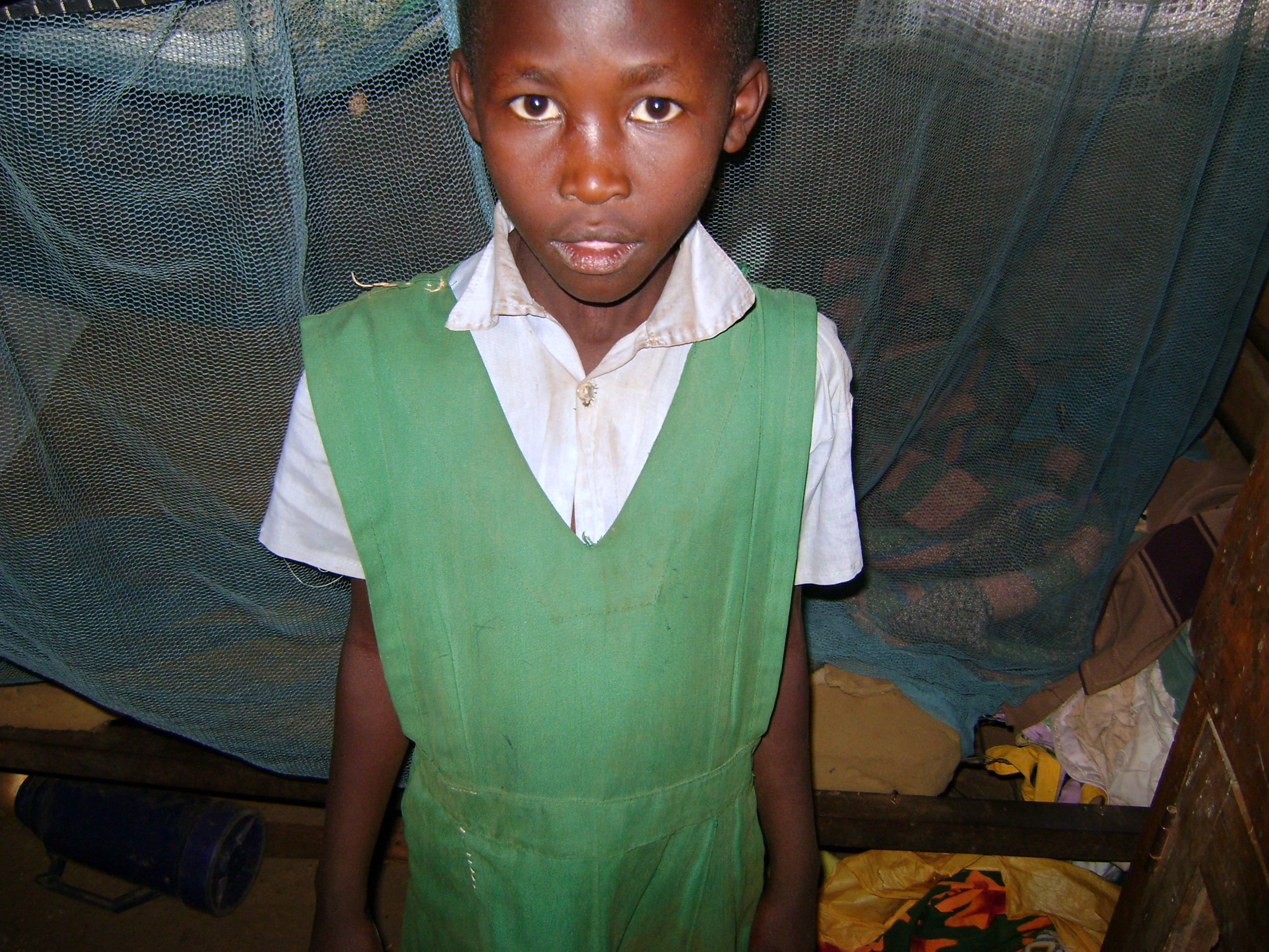 Wayua stands beside her bed. She has a mosquito net provided by the government