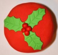 Cupcake recouvert de fondant rouge et décoré avec une feuille de gui en fondant
