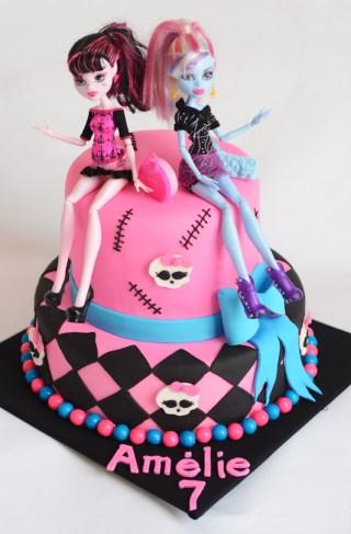 Gâteau sous le thème de ''Monster High'' pour une princesse de 7 ans! L`intérieur du gâteau est trois couleurs (vanille, chocolat, vanille rose) avec un glaçage crème au beurre à la vanille entre chaque couche. Il est recouvert de fondant et décoré avec deux barbies ''Monster High''.