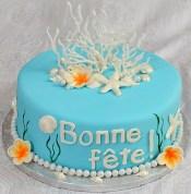 Gâteau 10'' au chocolat recouvert de fondant et décoré avec des coquillages et fleurs en pastillage.