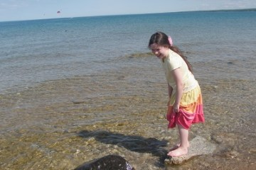 Girl standing on Rock over water
