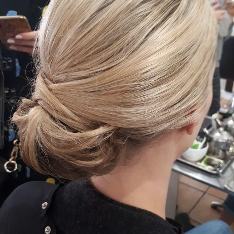 Blonde hair, bun at nape of neck