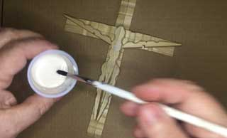 Use a paint brush to put a heavy coat of wood glue all over your crucifix.