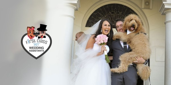 Bride and groom holding their pet dog at their wedding