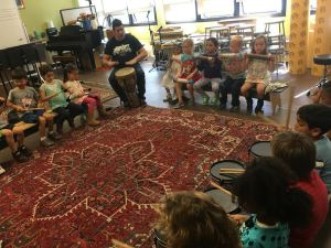Kindergarteners making music with Alfie Macias in their percussion circle