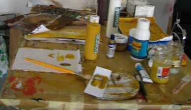 Du siehst einen Tisch mit Farben und Pinseln und Acrylfarben, die bei Mixed-Madia Arbeiten verwendet werden können.