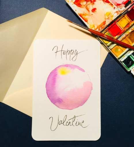 Man sieht die fertige Valentins-Karte, gemalt von der Künstlerin Dodo Kresse. Es ist eine rosa-gelbe Scheibe aus Aquarellfarbe und trägt den Titel Happy Valentine.