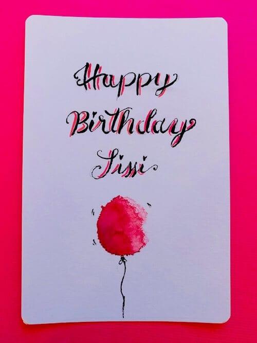 Happy Birthday wird auf eine Karte gelettert, dazu ein Luftballon gezeichnet