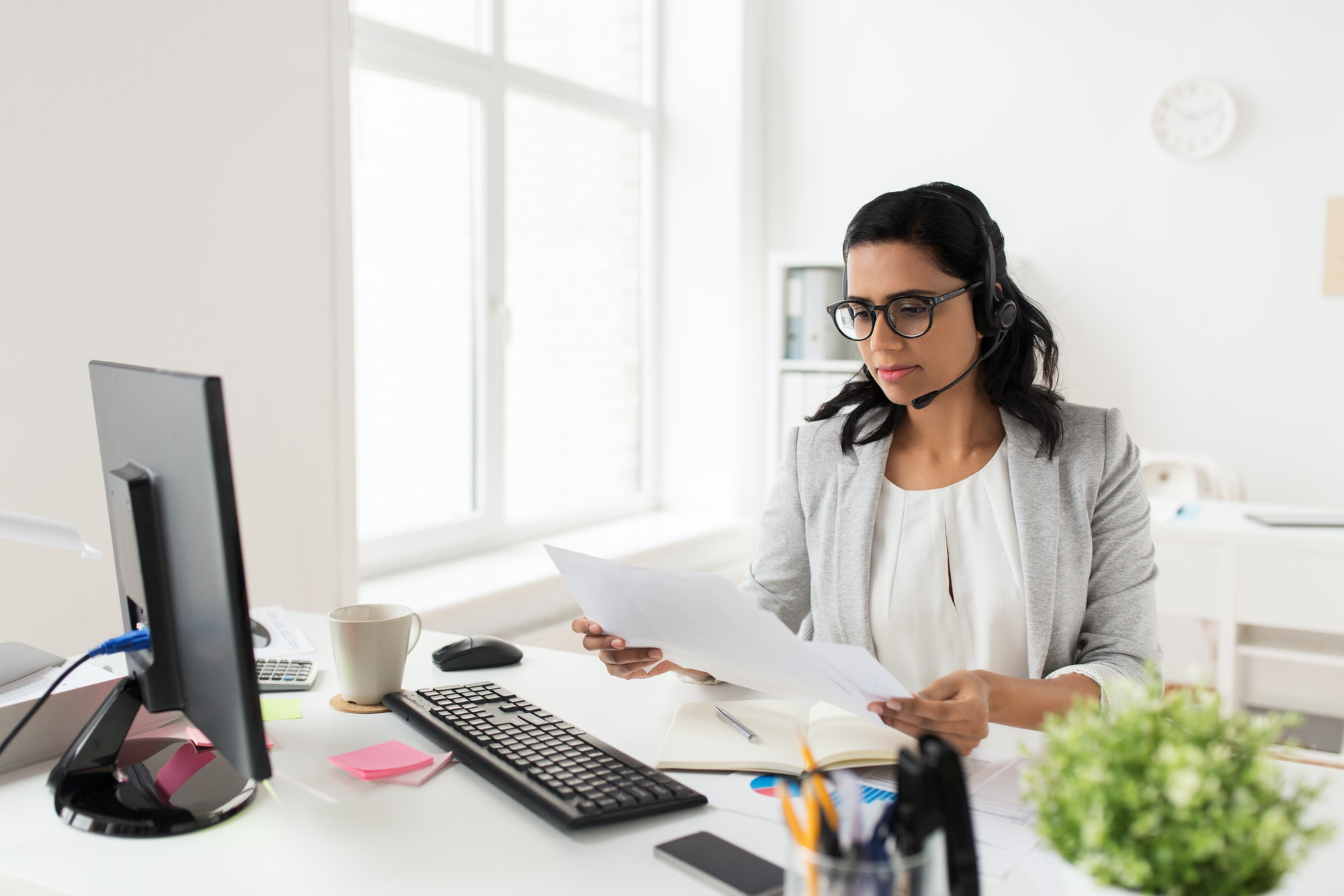 businesswoman with headset and papers at office