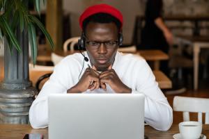 Black man in headphones watching educational webinar on laptop, online work in cafe. E-learning.
