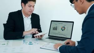 Teamwork with business people analysis cost graph on desk at meeting room.