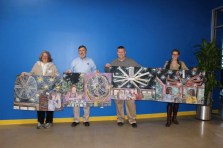 Julie Baldyga, an artist with Louisville's StudioWorks art program for special-needs adults, delivers four commissioned paintings to Big Ass Fans in Lexington, Ky. - Photo courtesy of Big Ass Solutions