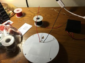 The bottom of the light enclosure with the black and red circuit extending wires.