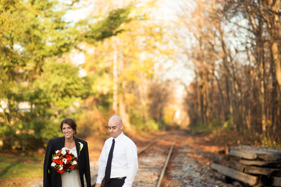 Bride wears grooms jacket as they walk on tracks