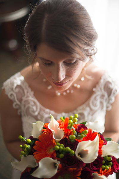Portrait of bride looking down at her Fall bouquet