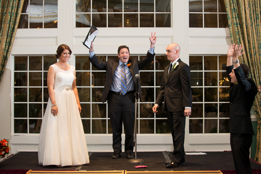 Officiant raises arms and celebrates marriage of couple at Mendenhall Inn