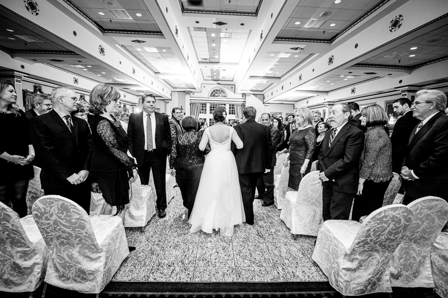 Shot from behind of bride being escorted down the aisle by mother and father for Mendenhall Inn wedding ceremony
