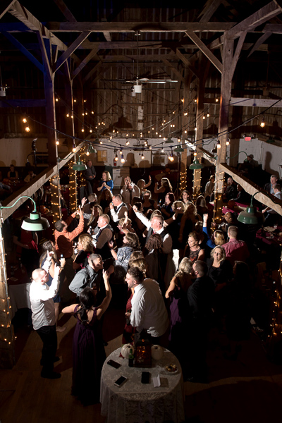 Spotlight on guests dancing at a barn reception