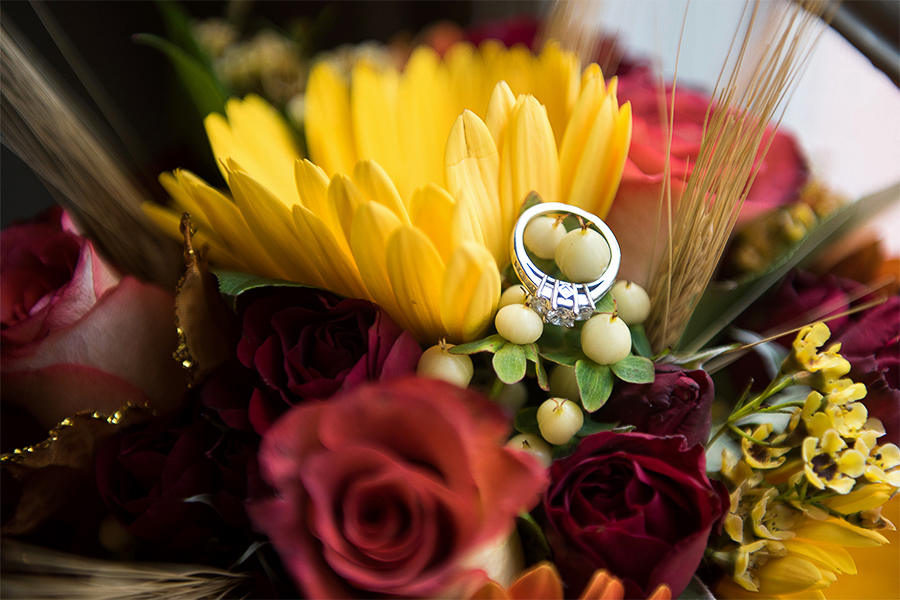 Engagement ring sitting on a fall bridal bouquet