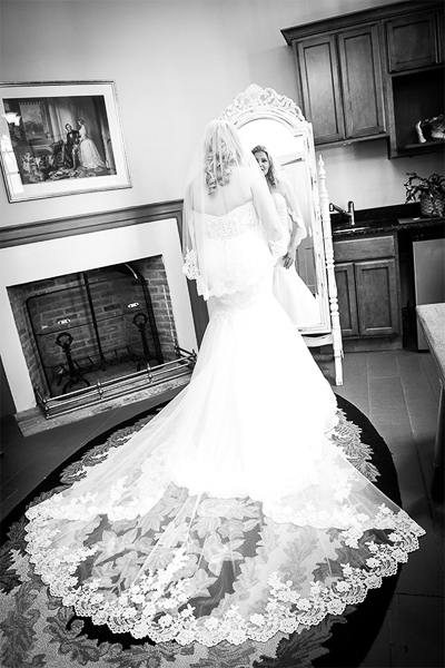 Bride in her wedding dress standing and looking into a tall mirror