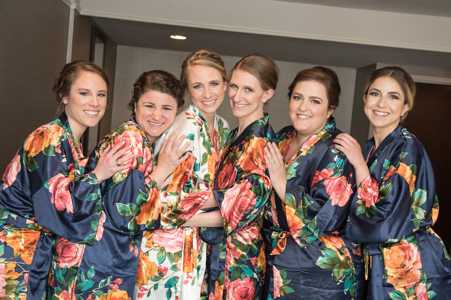 Bride and bridesmaids in floral robes getting ready for the big day