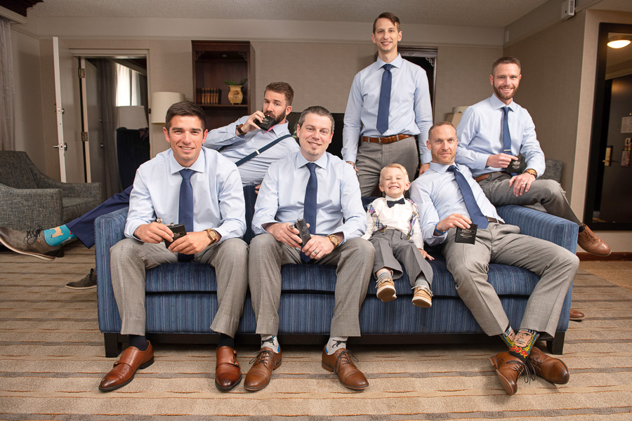 Groom and groomsmen casually posing on couch as they are prepping for the first look