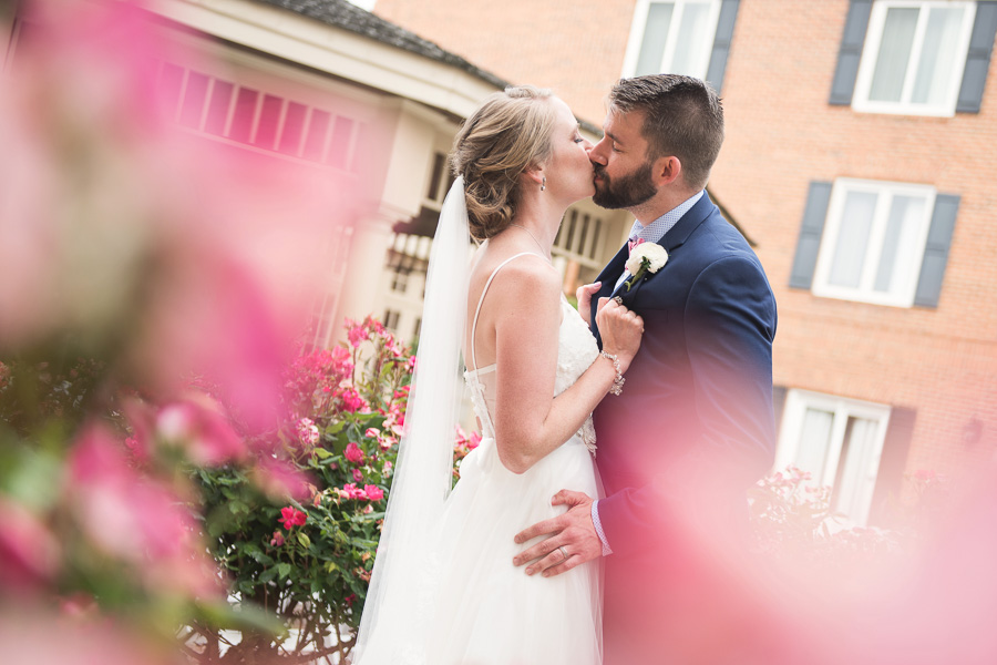 Pink flowers in the foreground, a bride and groom kiss in a hotel courtyard surrounded by flowers